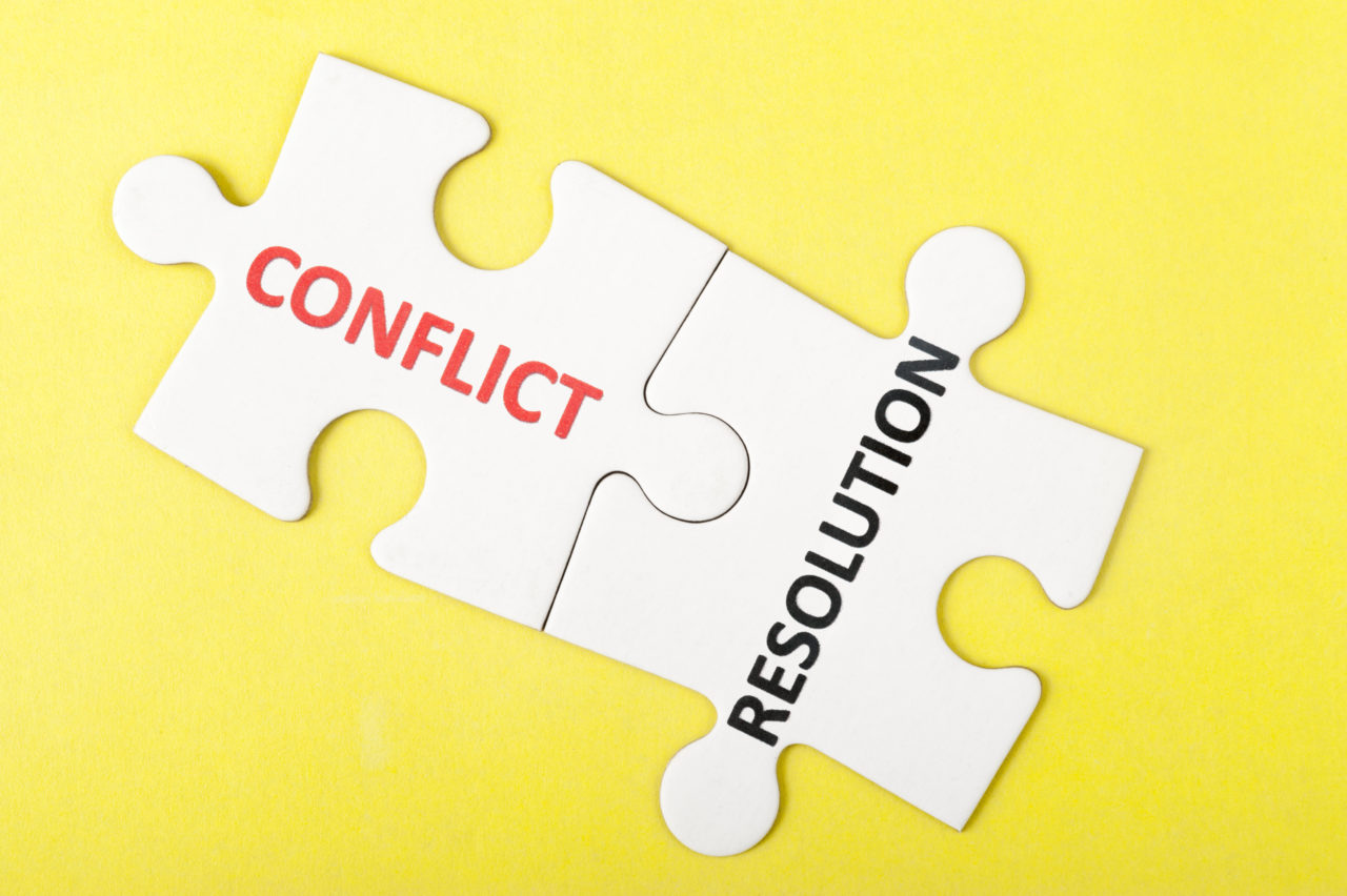 Conflict and resolution words printed on two pieces of puzzle